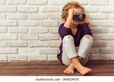 Beautiful little girl in casual clothes is taking a photo using a camera, sitting against white brick wall