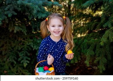 beautiful little girl child in the park with a basket of colorful Easter eggs laughing