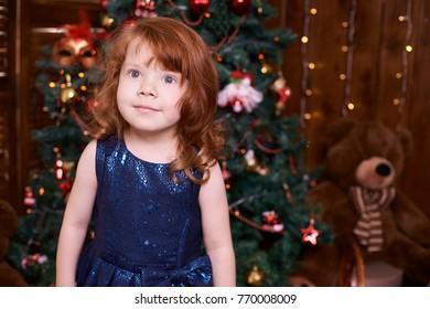 Beautiful little girl. Christmas interior. Blue dress.