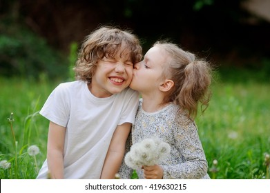 Beautiful little girl collects dandelions in the yard and kiss boy. Children play together in the summer.