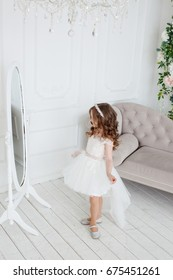 Beautiful little girl with curls and a white fluffy dress looks in the mirror
