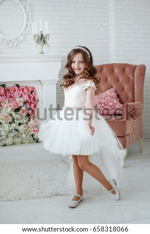 3c1d1897b6475 Beautiful little girl with curls and white Quinceanera dresses with a train  on the background of