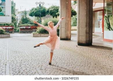 Beautiful little girl dancing under the rain, wearing soft ballerina dress