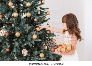 Beautiful little girl decorates huge Christmas tree for holiday celebration. Horizontal color photography.