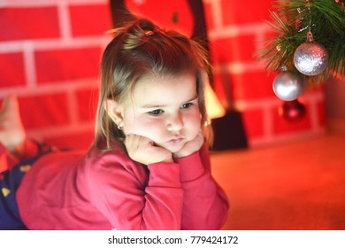 Beautiful little girl with decorations for Christmas evening. Cute little girl portrait in front of Christmas tree