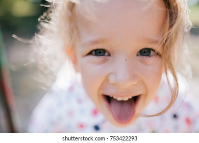 Beautiful little girl with deep blue eyes shows her tongue
