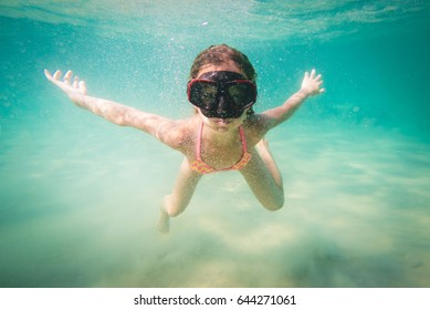 Beautiful little girl diving with mask underwater in the sea.