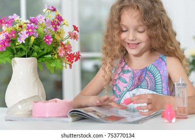 Beautiful little girl doing manicure at home