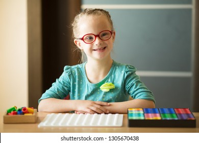 Beautiful little girl with Down syndrome is sitting in the classroom