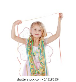 Beautiful little girl draped in party streamers as she celebrates a birthday or festival, isolated on white