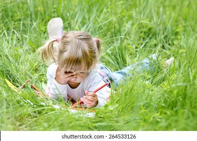 beautiful little girl draws on nature