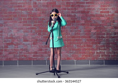 """Beautiful little girl in dress and """"MOTHER'S HEELS"""" with microphone on brick wall background"""