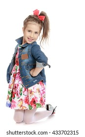 beautiful little girl dressed in colorful dress over which is worn Jean jacket. A girl stands on her knees - Isolated on white background