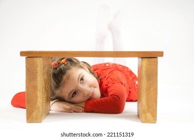 Beautiful little girl dressed in red playing and posing with light grey background