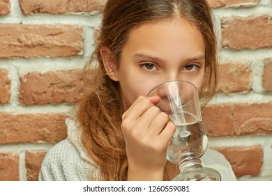 Beautiful little girl drinking water from glass mug against brick wall.