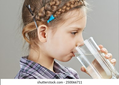 Beautiful little girl is drinking water, on gray background.