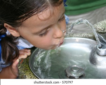 Beautiful little girl drinking water from a fountain.