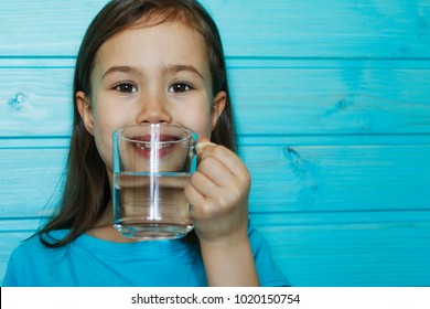 Beautiful little girl drinks clean water from a transparent glass on a blue background