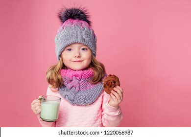 beautiful little girl drinks milk and eats cookies in a knitted hat and scarf on a pink background in the studio,christmas night