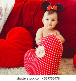 Beautiful little girl in ears of Minnie Mouse stands before red bed in bright room