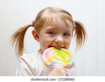 Beautiful little girl eating big colorful lollipop