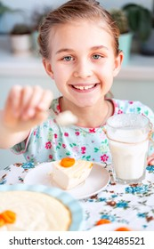 Beautiful little girl eating breakfast and drinking milk in kitchen at home