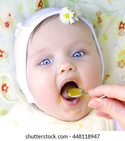 beautiful little girl eating first solid meal pumpkin puree with mouth wide open