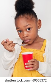 Beautiful little girl eating healthy yogurt