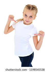A beautiful little girl in an empty white T-shirt points to herself. The concept of design of T-shirts, advertising of children's goods. Isolated on white background.