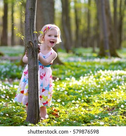 Beautiful little girl enjoying nature on a sunny day. Adorable child playing and hiking in the forest, covered with wild white anemones, early-spring flowers.