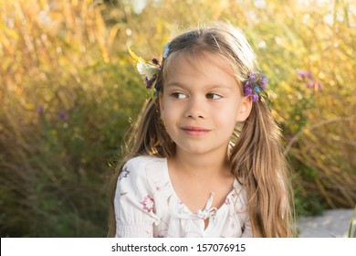 Beautiful little girl in a fall park with leaves and flowers woven in her hairs, with strong backlit