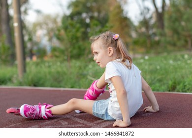 beautiful little girl fell on the rollers.A sad little girl lies on the asphalt . The child fell on roller skates.