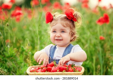 beautiful little girl in a field of poppies with strawberries