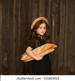 Beautiful little girl with French bread / baguettes. Dark background. Studio shot