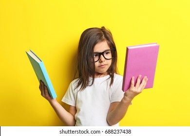 Beautiful little girl with glasses and books on yellow background