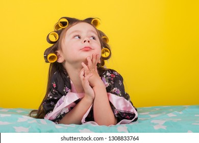 beautiful little girl in hair curlers on the bed