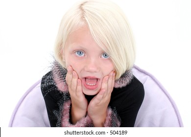 Beautiful Little Girl with Hands on Face Looking Shocked. Shot in studio over white.