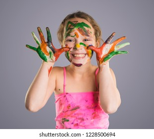 beautiful little girl with hands in the paint on the gray background