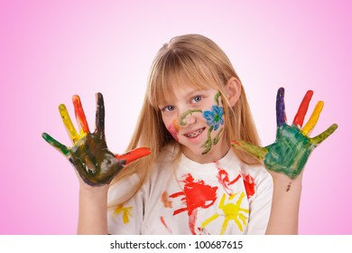 Beautiful little girl with hands painted in colorful paints over pink background