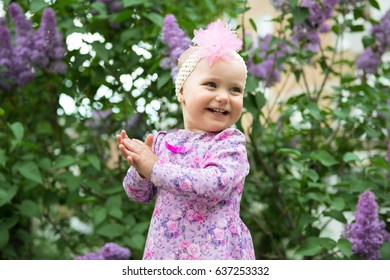Beautiful little girl happy smiling and claps her hands over lilac flowers in spring park. Childhood. Cute kid's face over nature background. Cheerful child's portrait, soft focus.