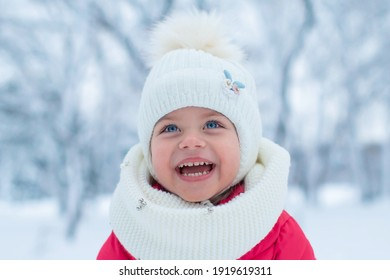 Beautiful little girl, has happy fun smile blue eyes, closed in white hat and scarf, red jacket. Child close up portrait. Lifestyle instagram concept. Fashion kid style. Amazing face. Winter snow.