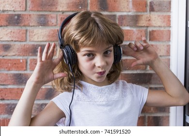 beautiful little girl with headphones at home listening to music and smiling, technology and music concept. Brick background. LIfestyle