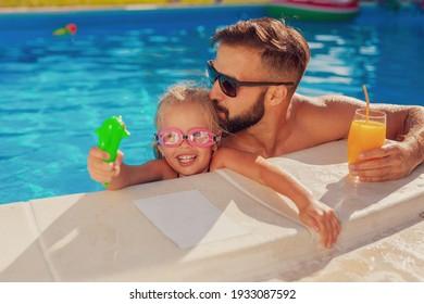Schönes kleines Mädchen und ihr Vater amüsieren sich an einem sonnigen Sommertag am Schwimmbad, Vater umarmt und küsst seine Tochter, während sie mit einer Rockpistole spielt