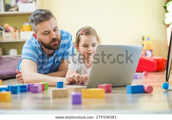 Beautiful little girl and her father with notebook