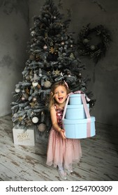 Beautiful little girl holding gift box. Child with Christmas gift. Happy xmas and New Year. Winter holiday concept. New year 2019 . My presents cocept.