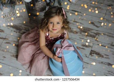 Beautiful little girl holding gift box. Child with Christmas gift. Happy xmas and New Year. New year 2019 . My presents cocept.