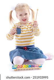 Beautiful little girl holding a hammer for xylophone.Isolated on white background, Lotus Children's Center.