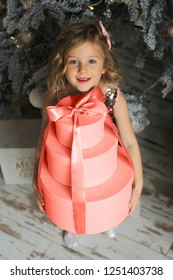 Beautiful little girl holding a pile of presents. Child with Christmas gift. Happy xmas and New Year, winter holiday concept. Color of the year 2019 Living Coral.