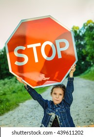 "Beautiful little girl holding red sign ""STOP""."