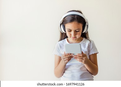 Beautiful little girl holding a tablet in her hands. The girl is wearing headphones. Online Learning.  Portrait isolated on a grey background.